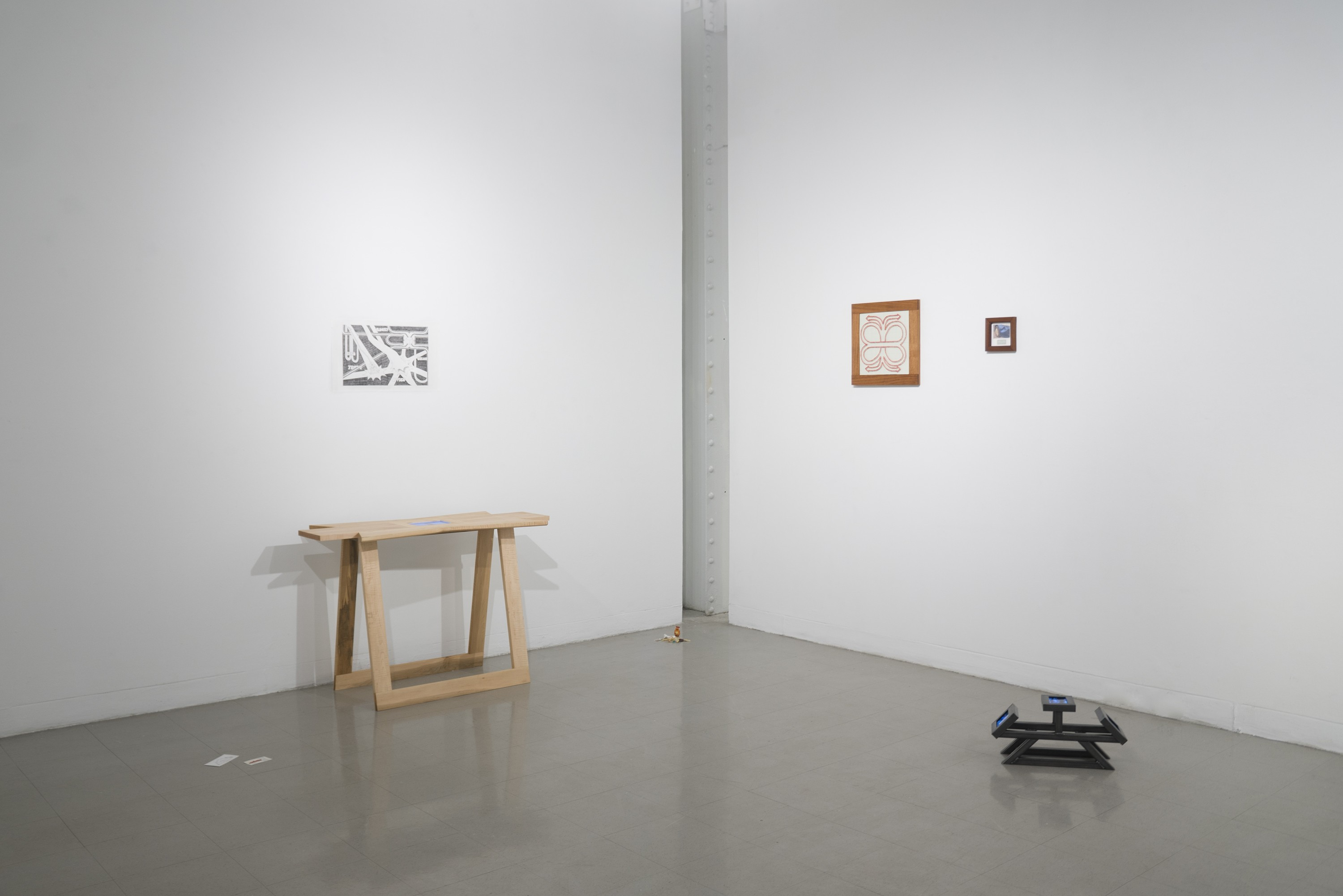 A photo of the whole show is installed in a gallery. From left to right: cards on the ground, a table with a screen in the tabletop and a drawing above, a pile of small objects on the ground, two wall-mounted framed works, and a small steel sculpture with