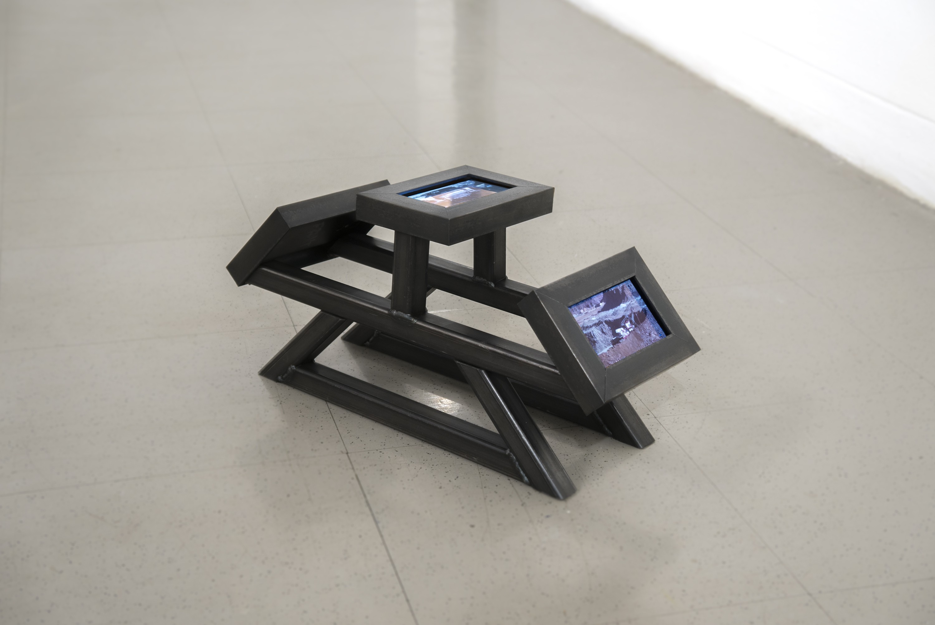 A floor sculpture consisting of a steel frame modeled after a car chassis holding three small screens. One screen faces forward, another up, and another backward. One plays a video of cars being scrapped, another plays a home movie of someone showing fri