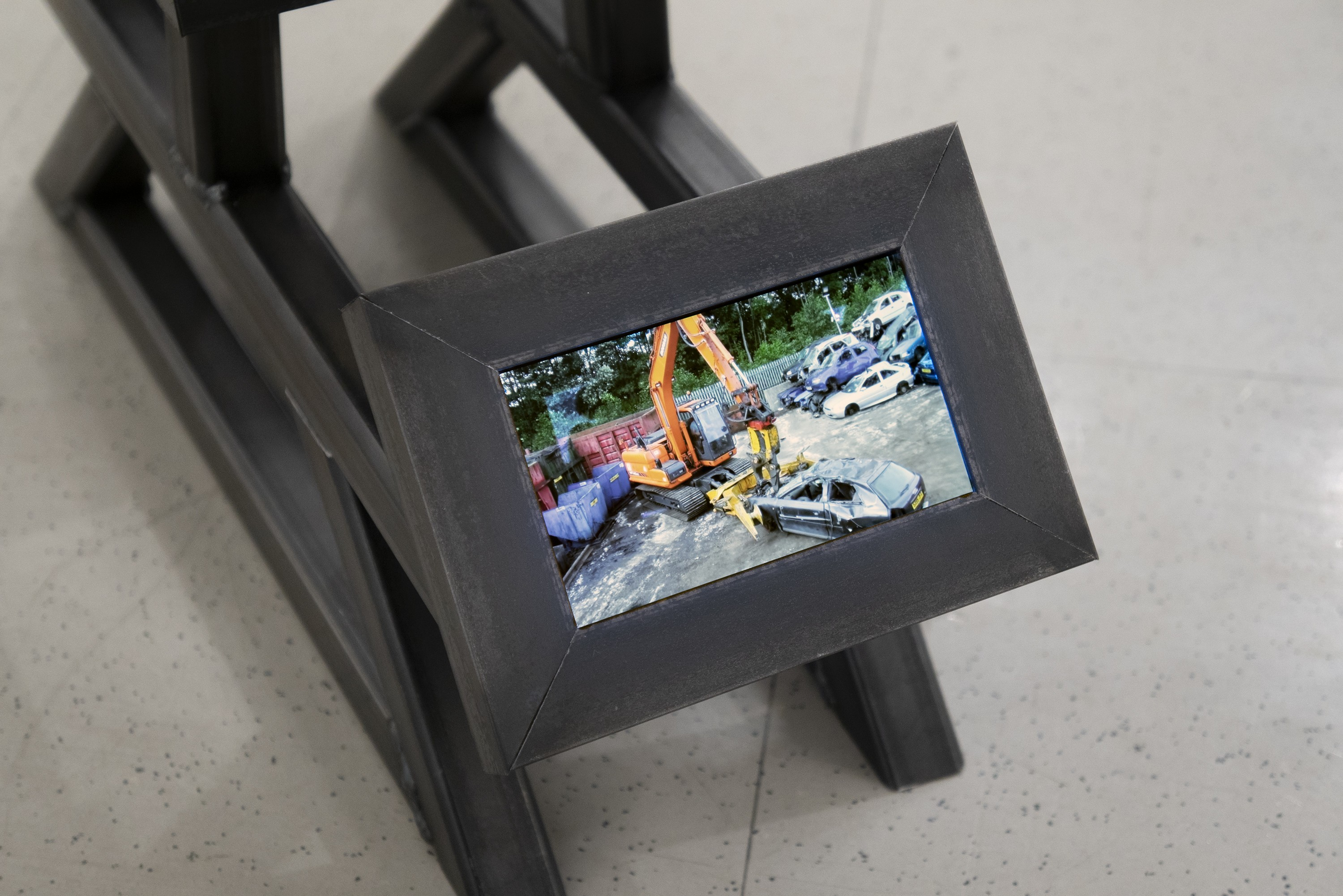 A floor sculpture consisting of a steel frame modeled after a car chassis holding three small screens. One screen faces forward, another up, and another backward. One plays a video of cars being scrapped, another plays a home movie of someone showing frie