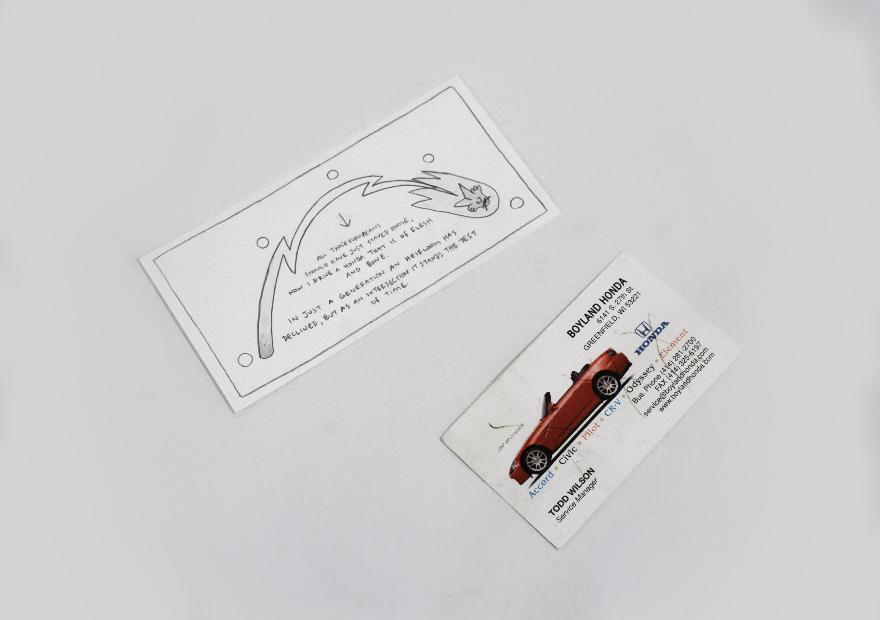 """A small hand-drawn paper card and a business card. The business card belongs to Todd Wilson, service manager at Boyland Honda. The hand-drawn card reads: """"All those Europeans should have just stayed home, now I drive a Honda that is of flesh and bone"""