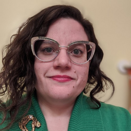 Headshot of Victoria Rose Pass wearing glasses and a green top