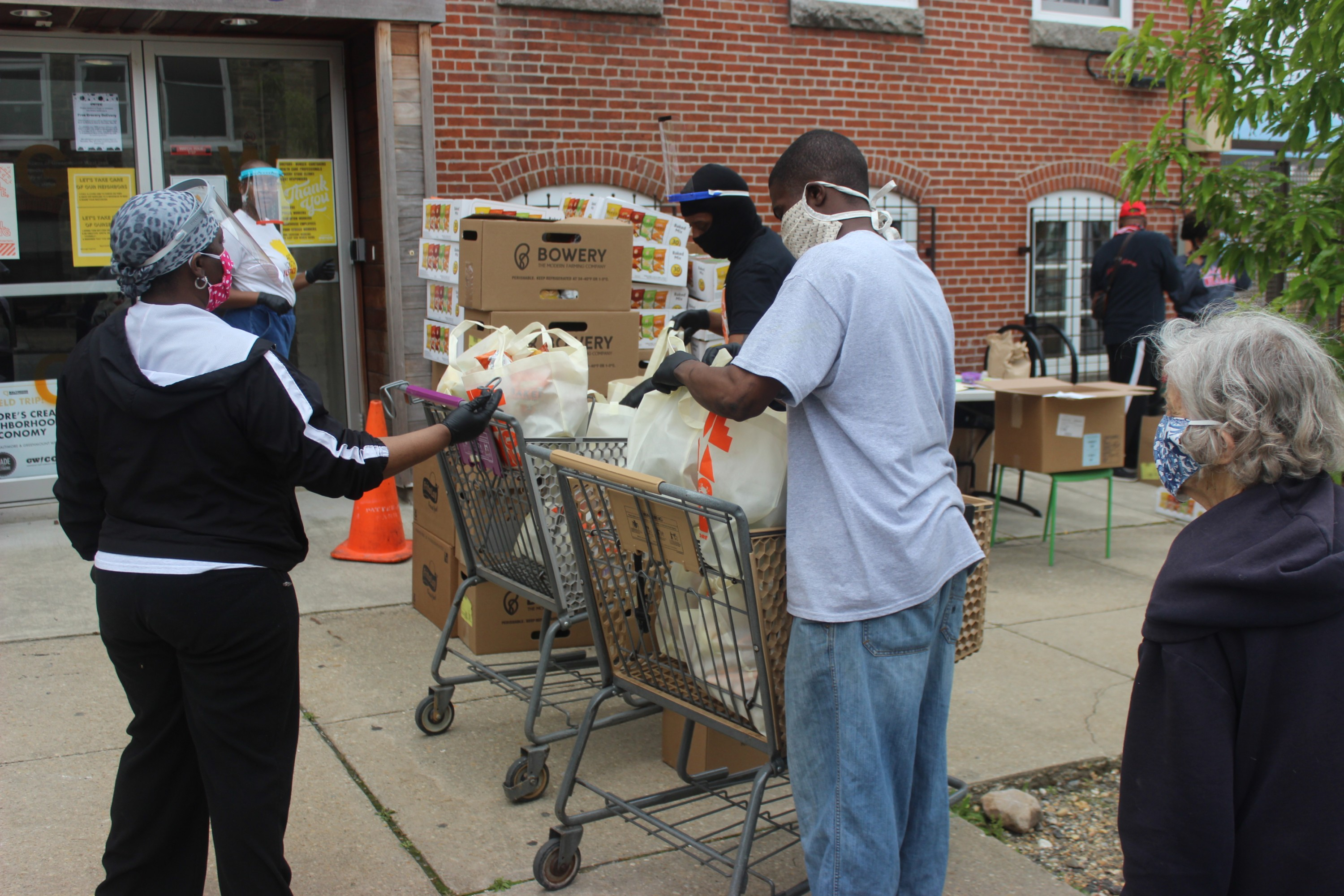 Residents in the Greenmount West community pick up boxes of donated food at the weekly Food Distribution program that the Greenmount West Community Center (GWCC) immediately set up when the pandemic began in March 2020.