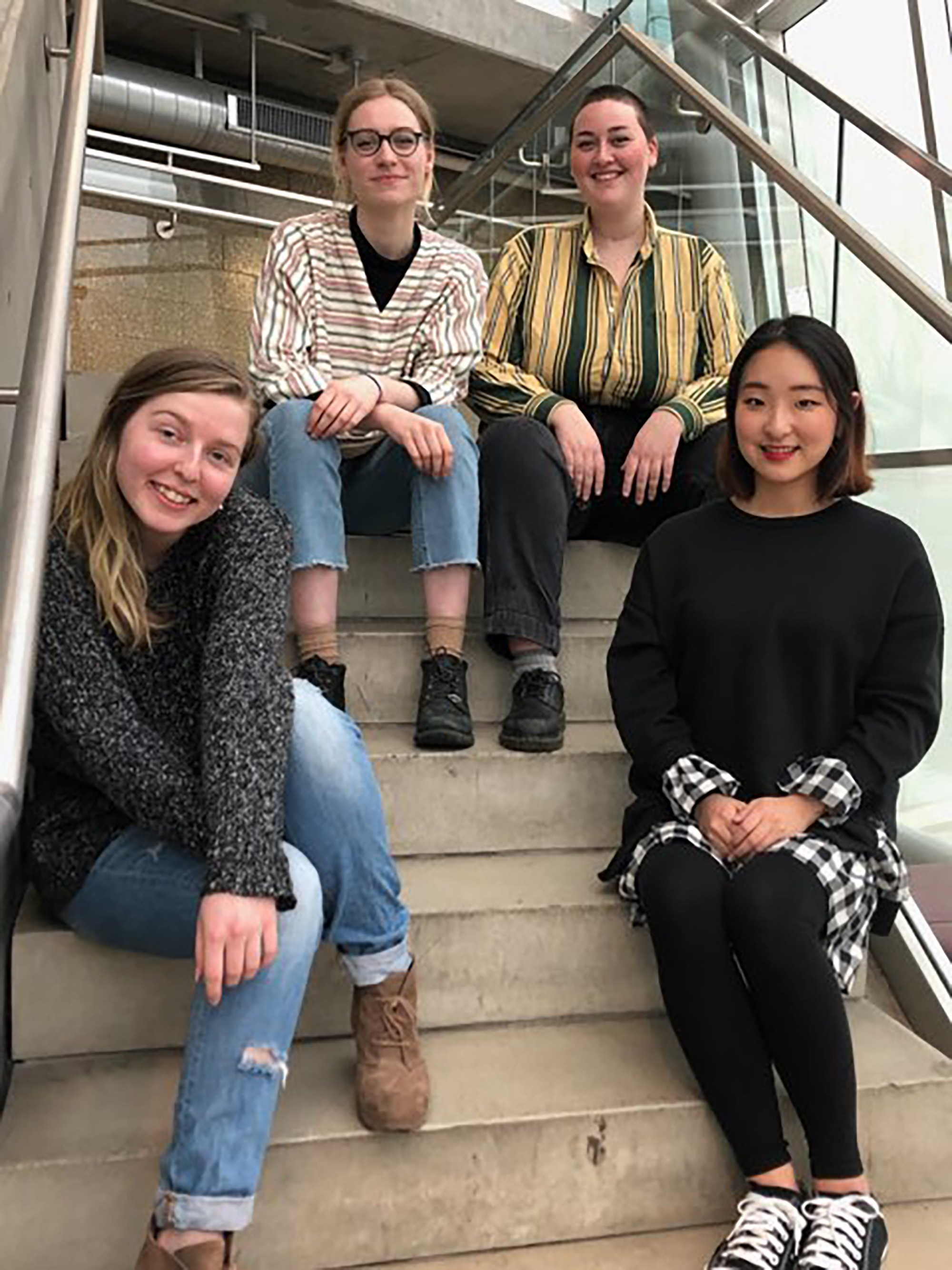 Four college students sitting on stairs and smiling