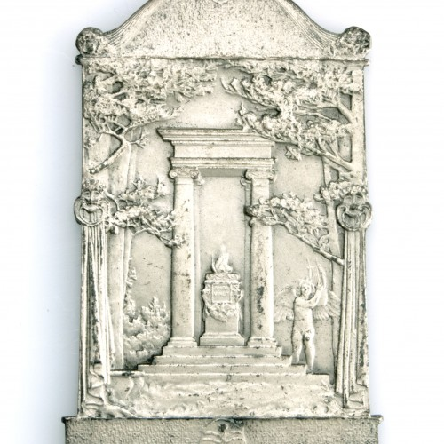 Artistic medal by Augustus Saint Gaudens featuring an engraving of an archway above steps and a fire at the center, an angel to the right, surrounded by trees.