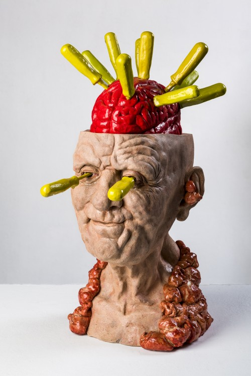 Sculpture of human head with with brain exposed pierced by yellow handled screw drivers