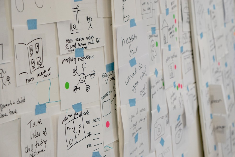 A photo of a wall full of sheets of paper with sketches of ideas.