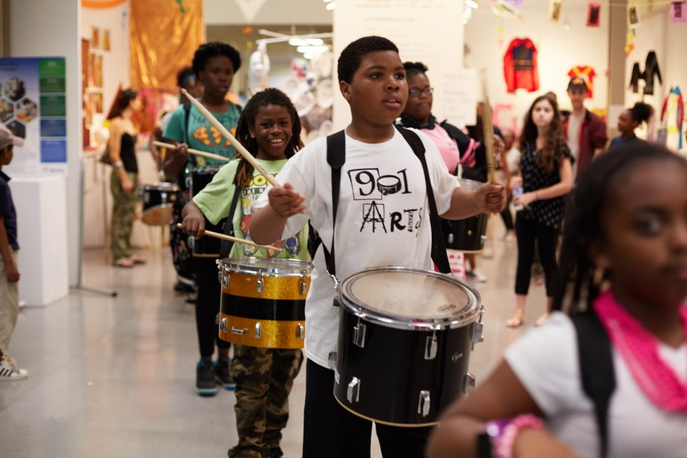 A drum line of elementary students marches through an exhibition space in the Bunting Center.