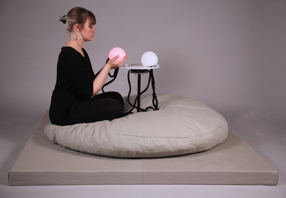 The artist sits on a large gray pillow with a glowing red orb in both her hands. Across the table from the artist is a second orb glowing white.