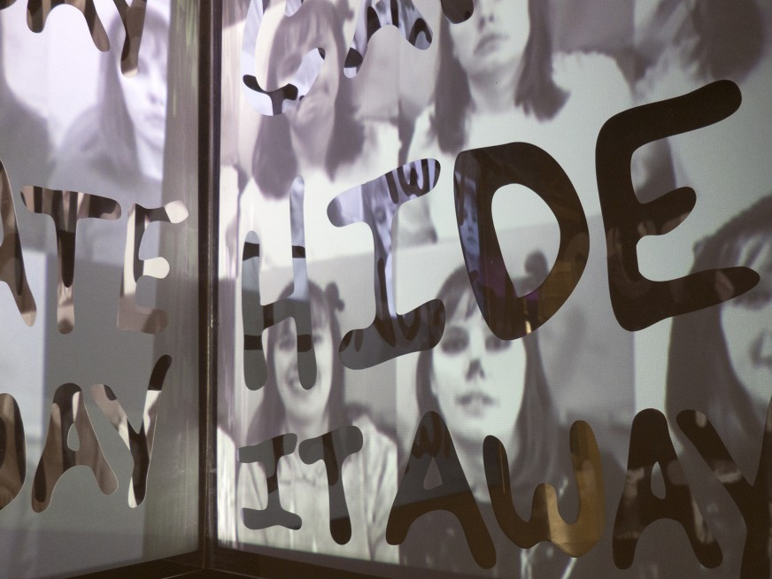 "Detail from a projection. Text overlay that says ""don't hide it away"" is superimposed on a grid of black and white portraits."
