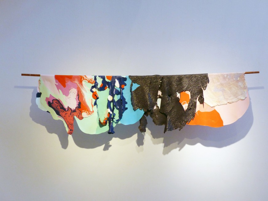 Dried acrylic paint in many colors is peeled from a flat surface is folded over a copper tube installed on a gallery wall.