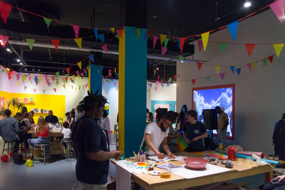 Busy exhibition space with colorful walls and activities.