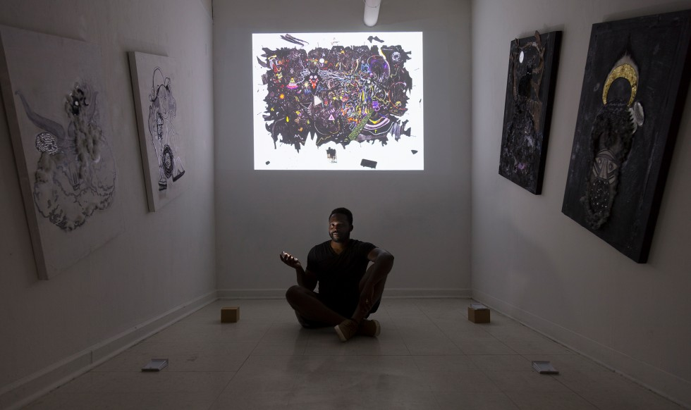 The artist sits in the middle of a darkened room. A projection of his work is behind him and four paintings line the walls on either side of him.