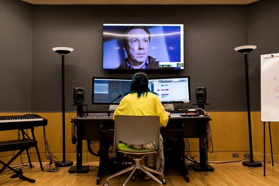 A student working in the recording studio. She is working on three large screens.