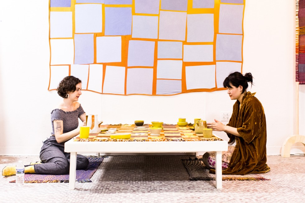 Two students sit a low table with a yellow ceramic tea set. Behind them is a large geometric fabric print.