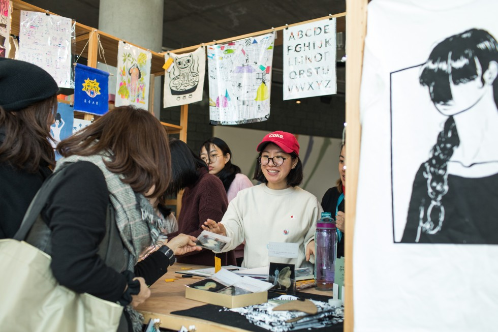 Students sell art from a decorated booth at Art Market.