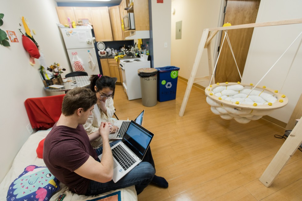 Two students work on laptops in a Meyerhoff House apartment.