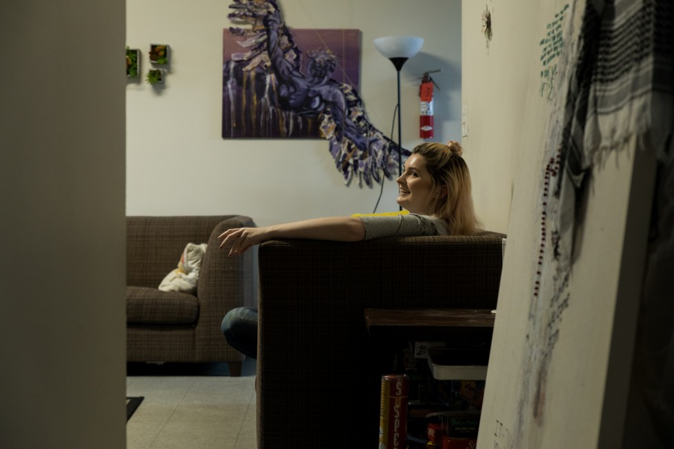 Shared space in a Spear Hall apartment. A student sits on a couch. Art hangs on the walls.