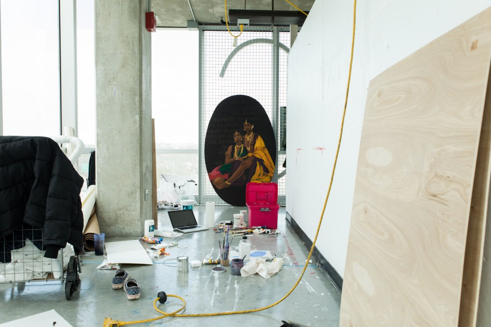 A residential studio in the gateway building. The space contains art making debris and a painting of two women in flowing fabric hangs at the back of the studio space.