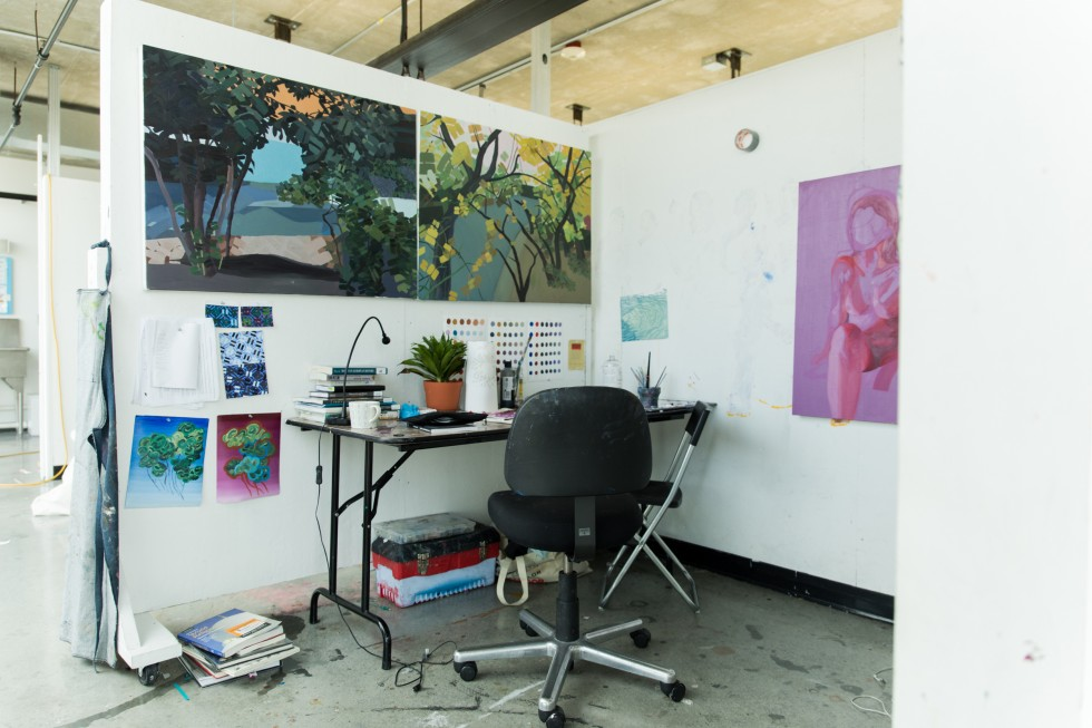 A painting studio with a desk. There are large paintings hanging on the walls.
