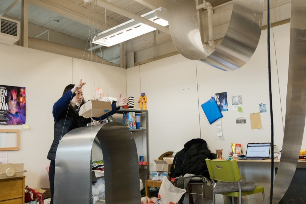 A grad student adjust a sculpture made of motors and sheet metal in her Lazarus Center studio