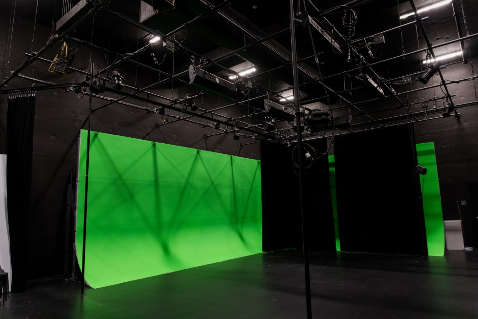 A large green screen hangs in a sound stage.
