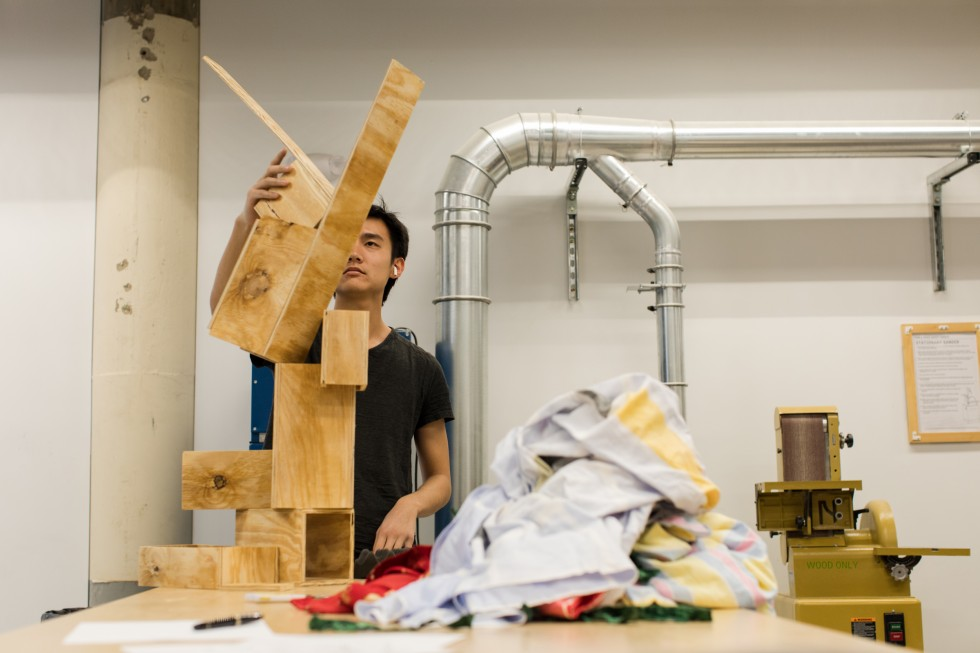 A student works on a sculpture made of wood.
