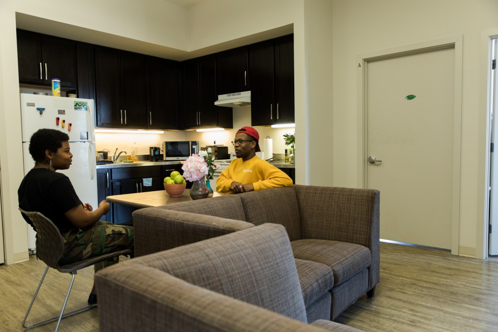 Two students talk at a table in a Leake Hall apartment.