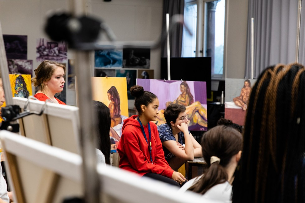 A group of students sits in front of paintings during a crit in a life drawing class.