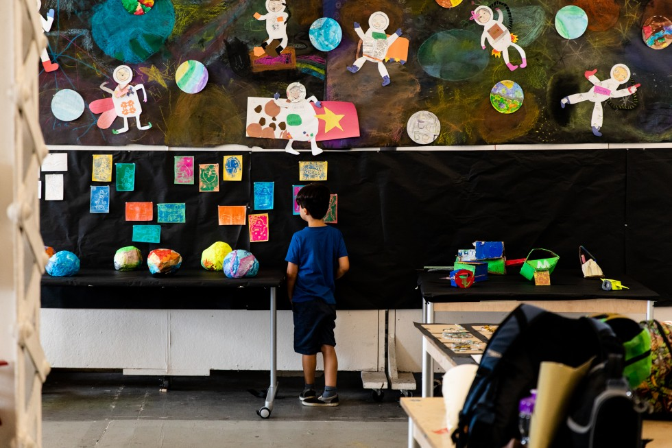 A young YPS student stands in front of a space-themed art display.