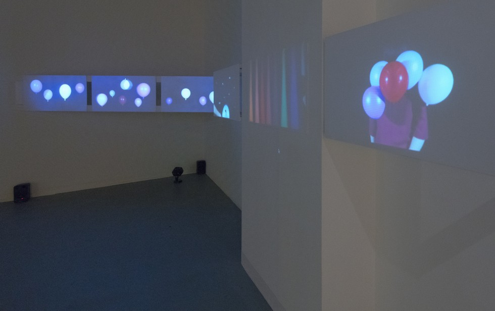 Installation of screens with video across all. Video stills include balloons and a person holding a bunch of balloons.