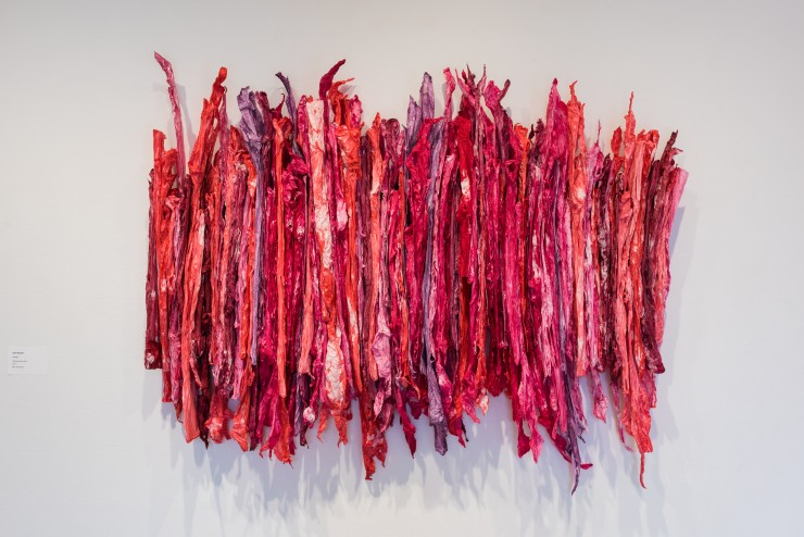 Collection of long strips of crumpled paper side by side. The paper is painted various shades of red, purple and pink.