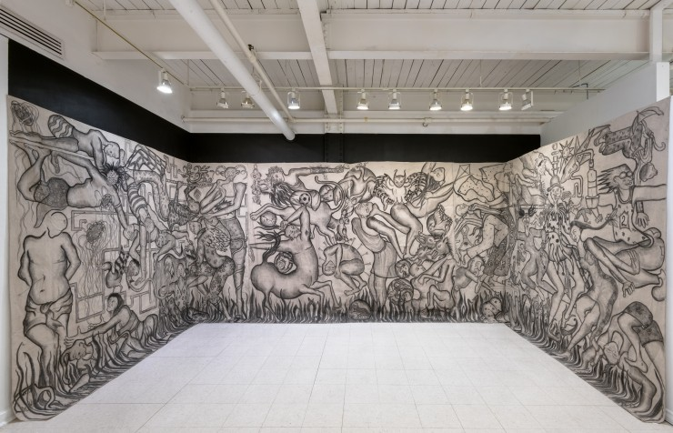 Three walls covered in canvas from floor to ceiling. The canvases are covered in charcoal and oil figures.