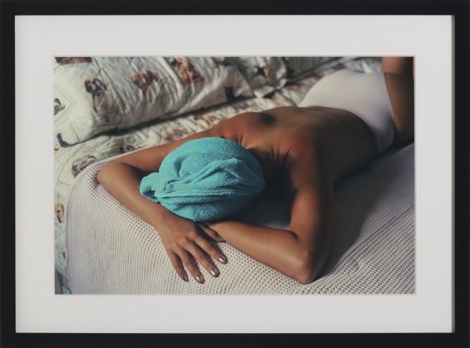 African American woman laying face forward on a bed half naked with a green towel on her head