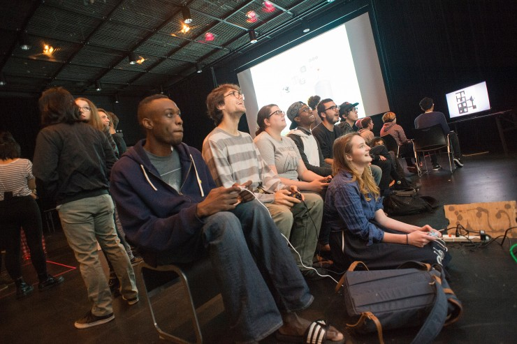 Students play video games on large projectors in a large space.