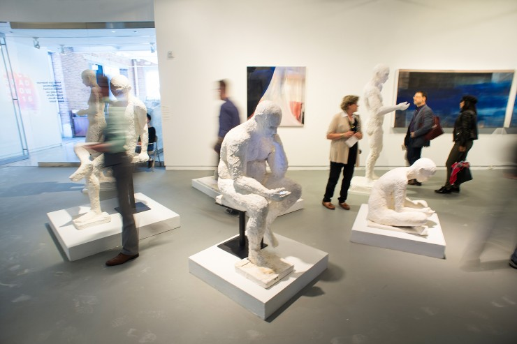 A bust gallery space with large white figures--some viewing their phones.