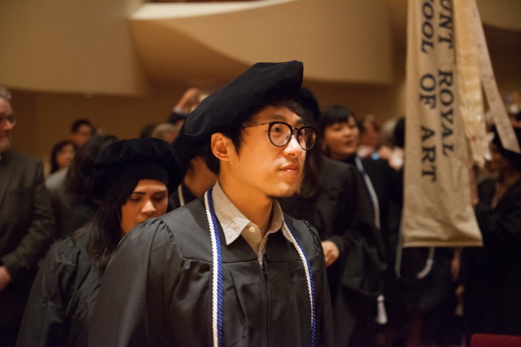 A student in a cap and gown at the Graduate Commencement Ceremony.