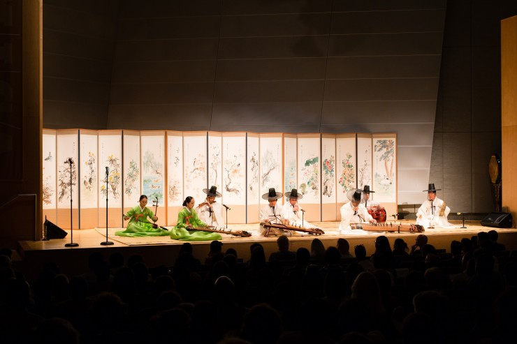 Musicians in traditional Korean dress perform on stage.