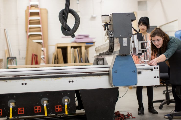 Two students work on a large wood cutting machine in the Digital Fabrication Lab.