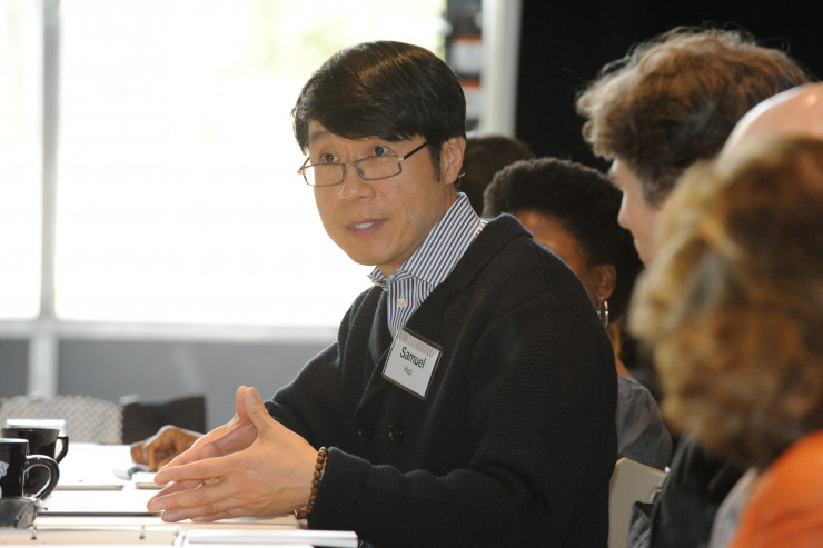 Samuel Hoi engaged in conversation with a large group around a table.