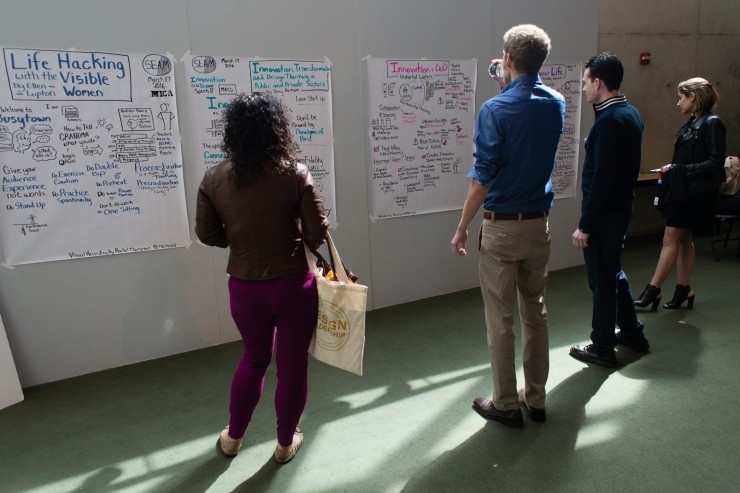 Conference attendees looking at information sketches on the wall.