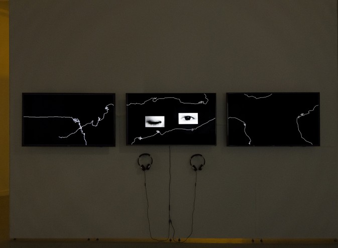 Three screens with headphones beneath. The left and right screens show scribbled white lines on a black background. The center screen contains cut outs of a pair of eyes that appear to be winking.