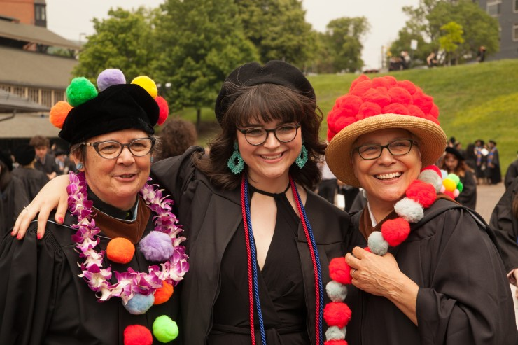 A student with faculty members at Undergraduate Commencement.