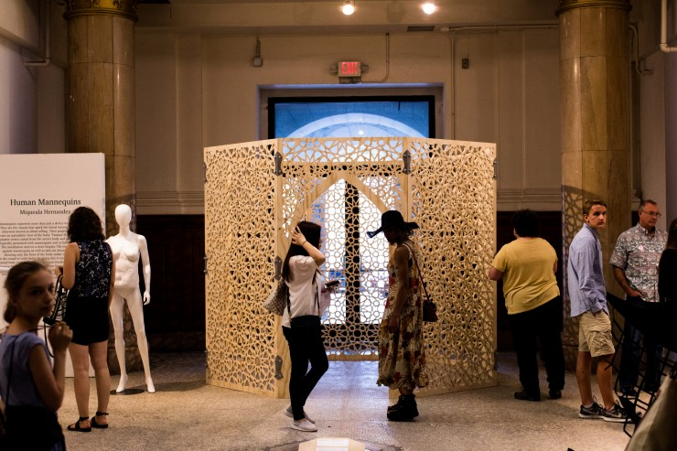 Visitors stand in the Middendorf Gallery during Artwalk. A large sculptural pavilion with intricate patters carved into the wood is in the background.