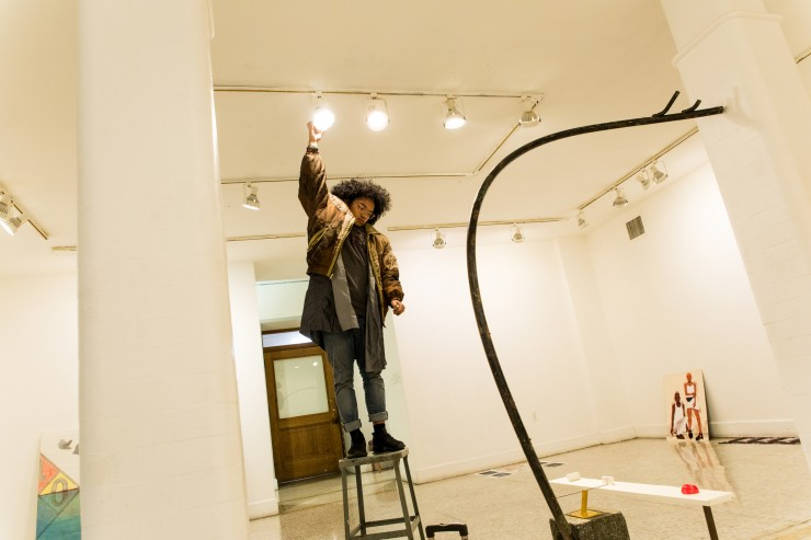 A student adjust lighting in a gallery space