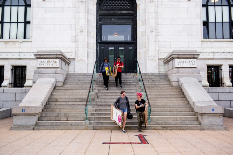 Students walking down the stairs of the Main Building carrying art.