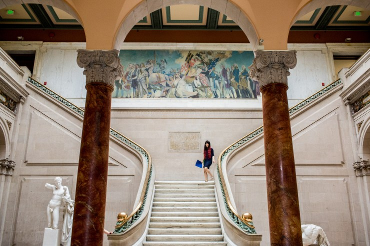 A student walks down the staircase in the Main Building.