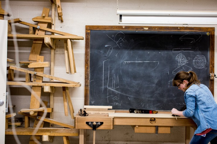 A student planes wood in the Wood shop. Behind her is a large chalkboard.