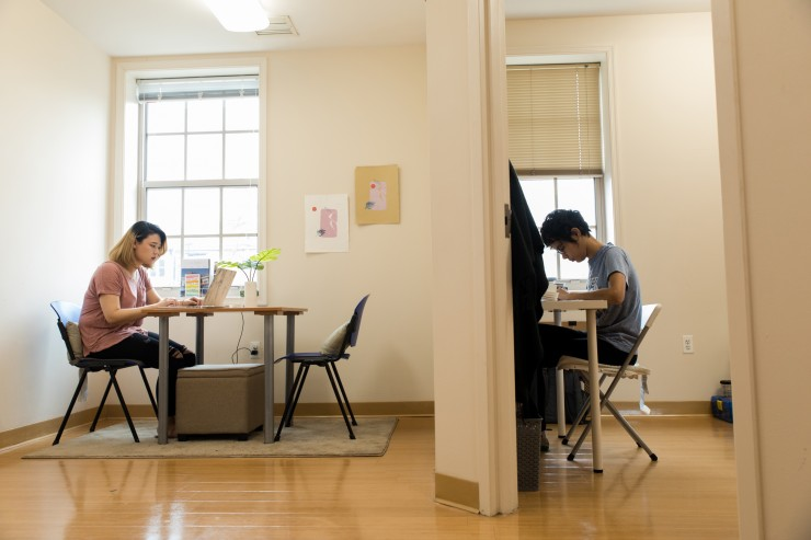 Two students work at desks in a Meyerhoff House apartment.