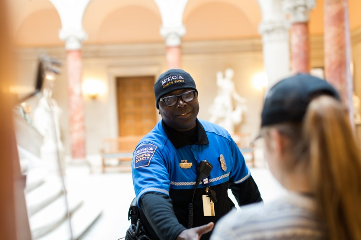 A Campus Safety officer greets a student in the lobby of the Main building.