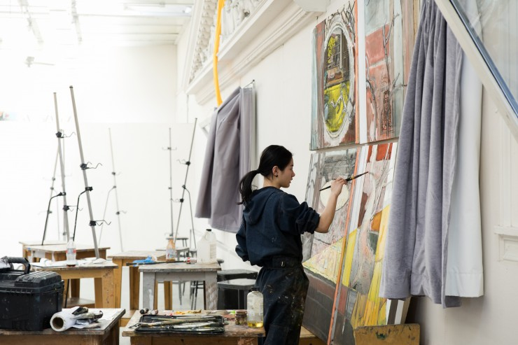 A student works on one of four large canvases propped against a wall in the Main Building.
